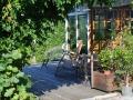 Sitzplatz eigerahmt von Topfpflanzen und Kletterpflanzen an der Gartenhütte, Holzterrasse