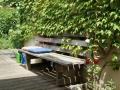 gemütlicher Sitzplatz unter Wein, Holzterrasse