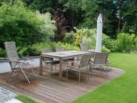 Holzterrasse und Möbel fügen sich wunderbar in den Garten ein