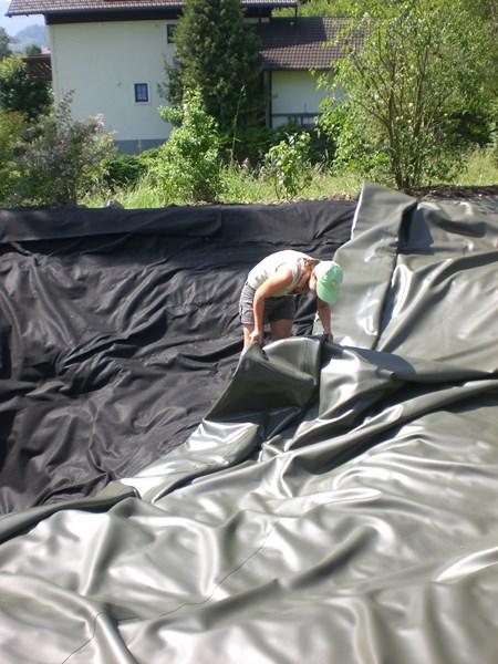 Biotopbau - auflegen der Folie, hier Maßanfertigung