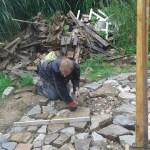 Flo beim Pflastern – dahinter wartet schon das Grillholz auf seinen Einsatz