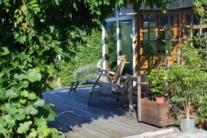 Sitzplatz eingerahmt von Topfpflanzen und Kletterpflanzen an der Gartenhütte, Holzterrasse